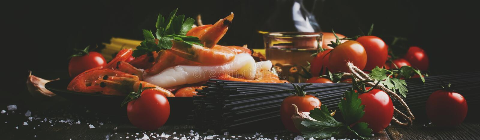 Ingredients for the preparation black pasta with seafood, tomatoes and white dry wine, black food cooking background, still life,. Banner, selective focus stock images