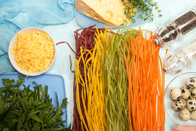 Ingredients for preparation dinner. Overhead of pasta tagliatelle of different colors, quail eggs, gouda cheese, honey mushrooms stock images