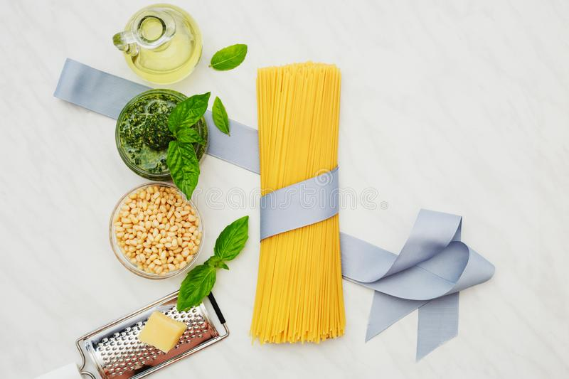 Ingredients for the preparation of Italian pasta with pesto sauce: raw spaghetti, olive oil, pine nuts, basil, parmesan cheese, stock images