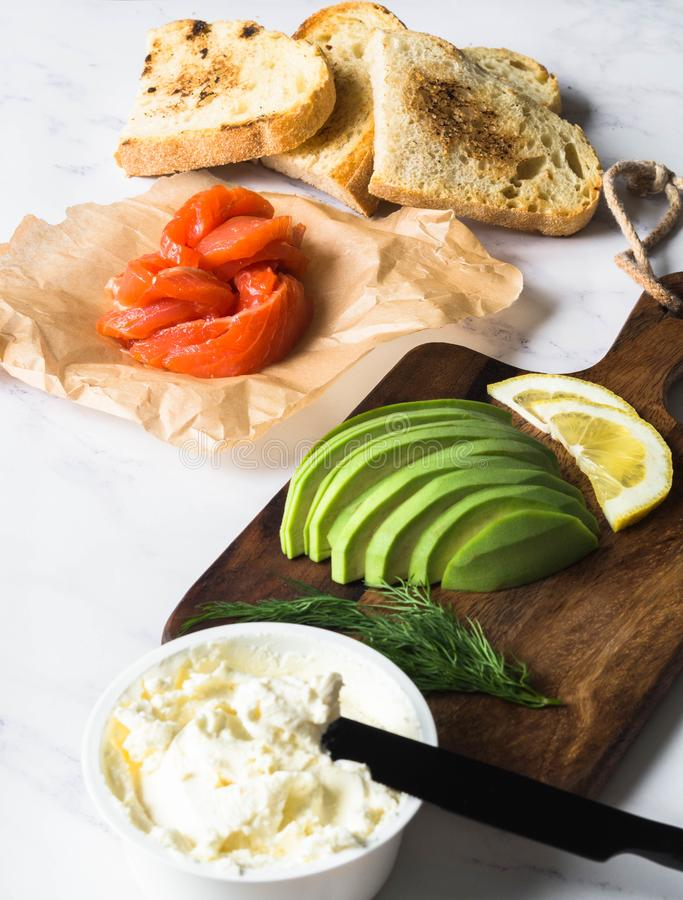 Ingredients for preparation sandwiches with cream cheese, salmon, avocado on grilled toasts on white marble background. Copy space royalty free stock photo