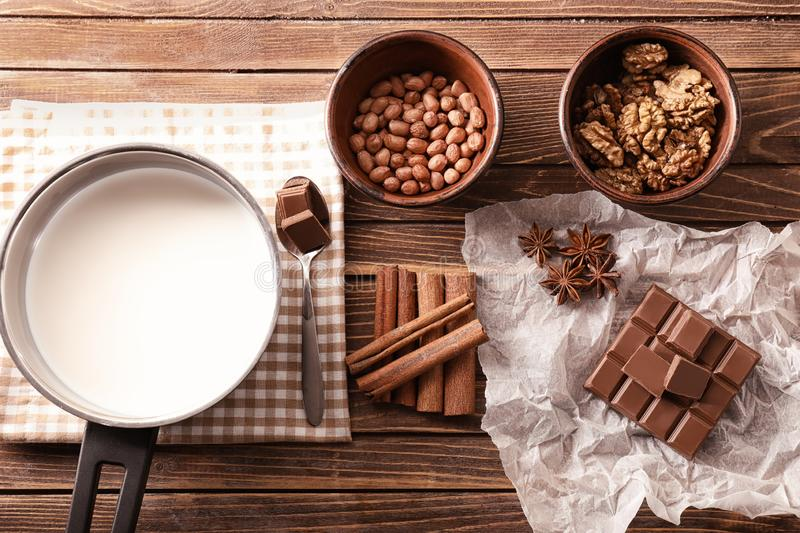 Ingredients for preparing of hot chocolate with nuts on wooden table royalty free stock photography
