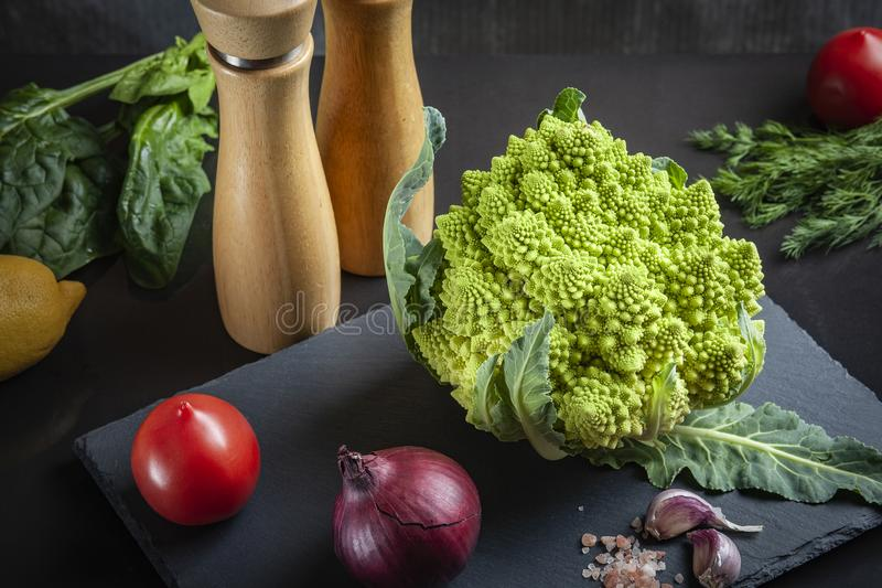 Concept of organic food with fresh vegetables: Romanesco broccoli, ripe tomatoes, red onion. royalty free stock photos
