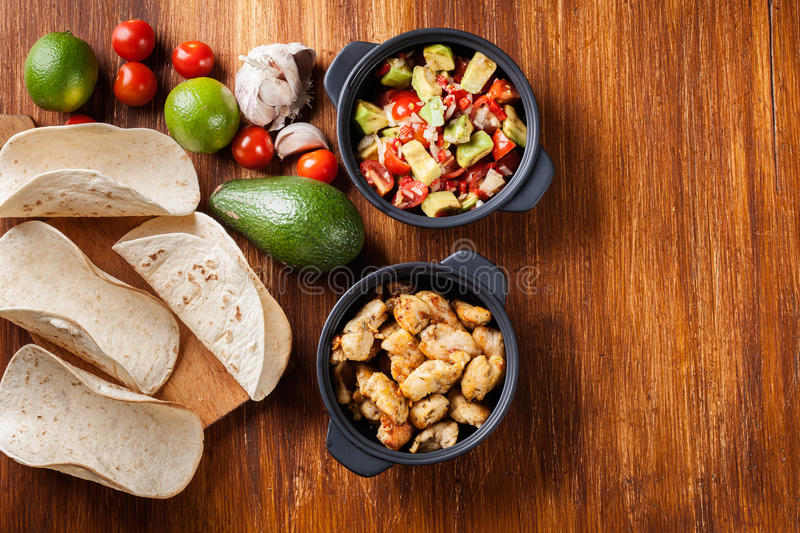 Ingredients ready for preparing chicken tacos with salsa made fr. Om avocado, tomatoes, and chilli peppers. Mexican cuisine. Top view stock photos