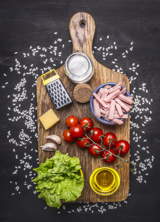 Ingredients for risotto with ham, vegetables and spices on a cutting board on wooden rustic background top view close up. Ingredients risotto with ham royalty free stock image