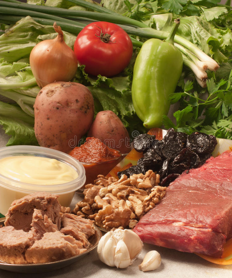 Ingredients for roast meat. A kitchen scene with all the ingredients for roast meat. Raw meat, vegetables, prunes, walnuts, garlic, mayonnaise and plenty of stock photography