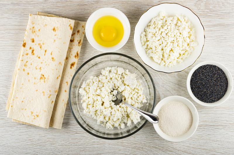 Ingredients for rolls - cottage cheese, poppy, egg, sugar, pita bread on wooden table. Top view. Ingredients for cooking rolls - cottage cheese, poppy, raw egg stock photos