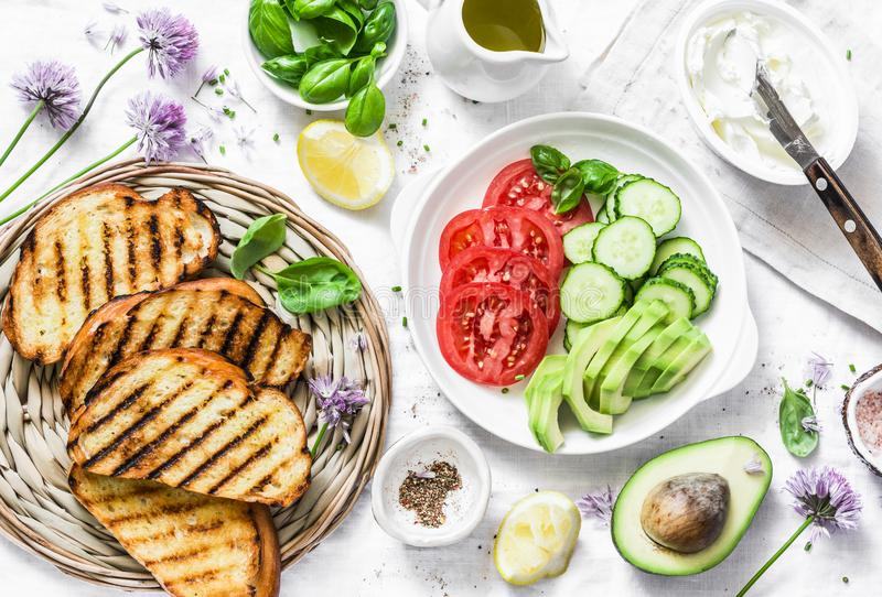 Ingredients for sandwiches - cream cheese, grilled bread, avocado, tomatoes, cucumbers, chives on a light background, top view. Su royalty free stock images