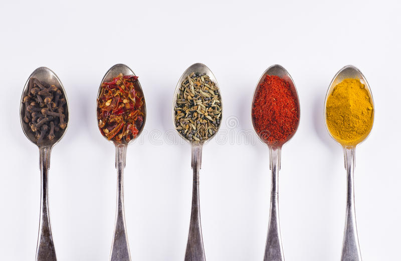 Ingredients spices 3 in spoons isolated on white background. Curcuma tumeric, tandoori masala, panch puren, sweet red pepper, cloves stock photos