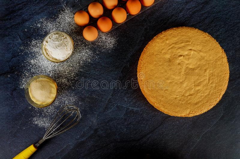 Ingredients for sponge cake. Ready cake on black background. Ingredients for sponge cake. Ready round cake on black background, dough, cooking, egg, sugar stock photo