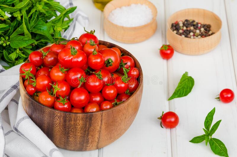 Ingredients for summer vegetable salad with cherry tomatoes, basil herb, olive oil and salt in on a wooden bowl. White wooden background. Rustic style stock photo