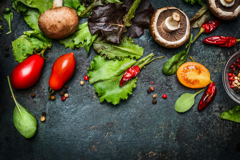 Ingredients for tasty salad making: lettuce leaves,champignons, tomatoes, herbs and spices on dark rustic background, top view royalty free stock photos