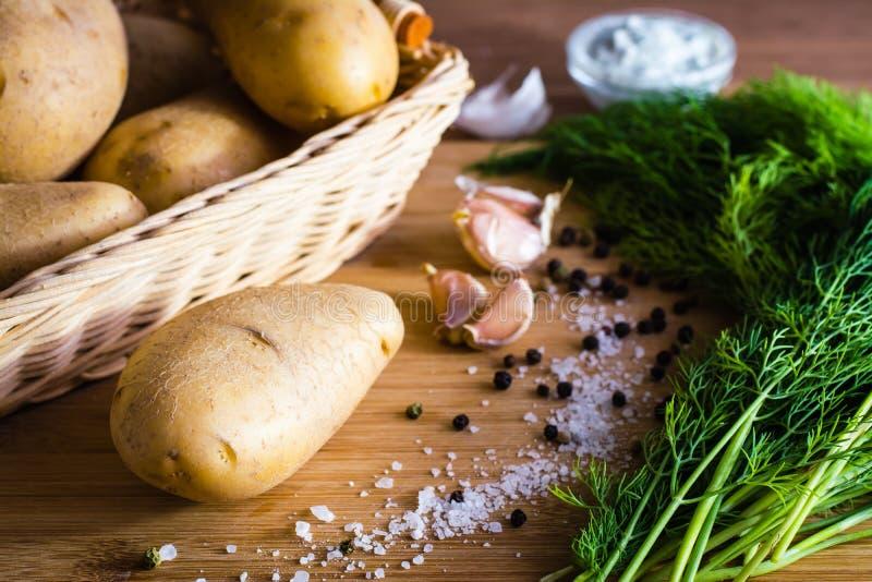 Ingredients to prepare potato dishes: tubers, garlic, dill stock photos