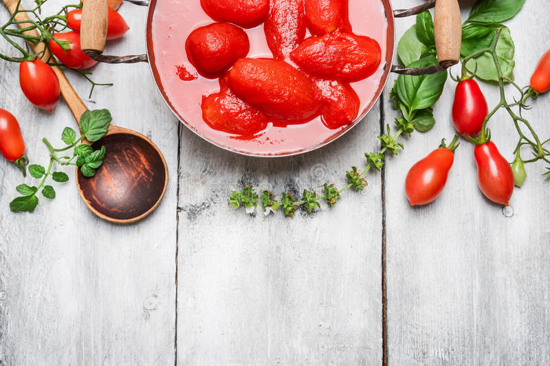 Ingredients for tomato sauce - fresh and peeled tomatoes, basil and spoon on white wooden background, top view royalty free stock images