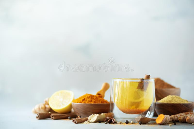 Ingredients for turmeric hot tea on grey background. Healthy ayurvedic drink with lemon, ginger, cinnamon, turmeric. Immune stock photo
