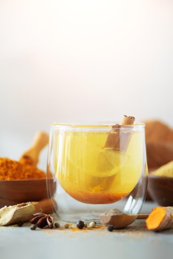 Ingredients for turmeric hot tea on grey background. Healthy ayurvedic drink with lemon, ginger, cinnamon, turmeric. Immune royalty free stock photos