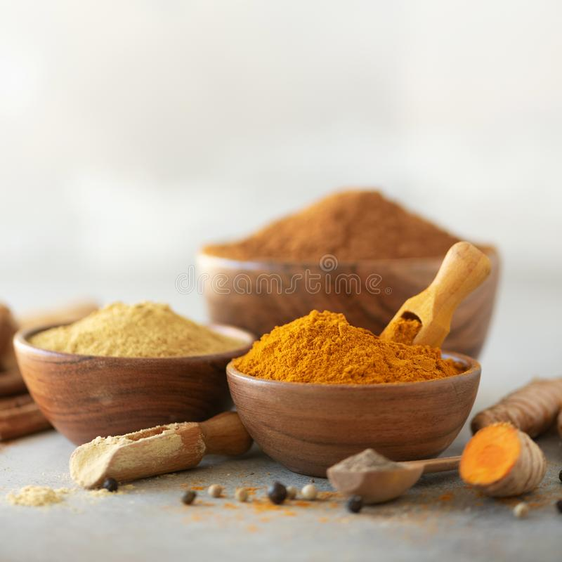 Ingredients for turmeric latte. Ground turmeric, curcuma root, cinnamon, ginger, black pepper on grey background. Spices stock images