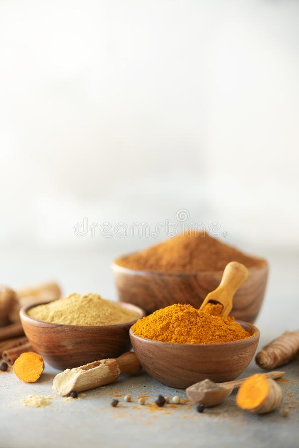 Ingredients for turmeric latte. Ground turmeric, curcuma root, cinnamon, ginger, black pepper on grey background. Spices royalty free stock images