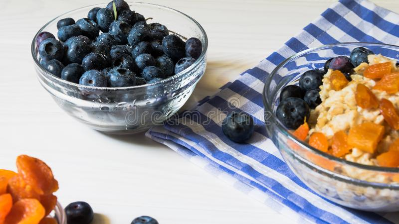 Ingredients for a wholesome healthy breakfast. Fresh blueberries, dried apricots and oatmeal stock photography