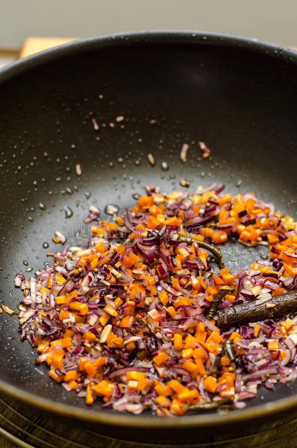 Ingredients in a wok. Small chopped vegetables and spices in a wok stock photography