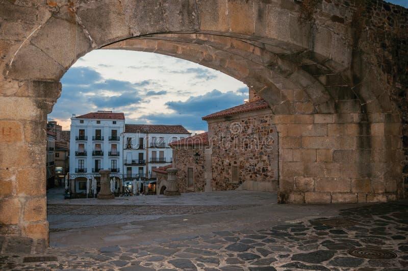 Ingresso di pietra incurvato e vecchie costruzioni al crepuscolo a Caceres fotografie stock libere da diritti