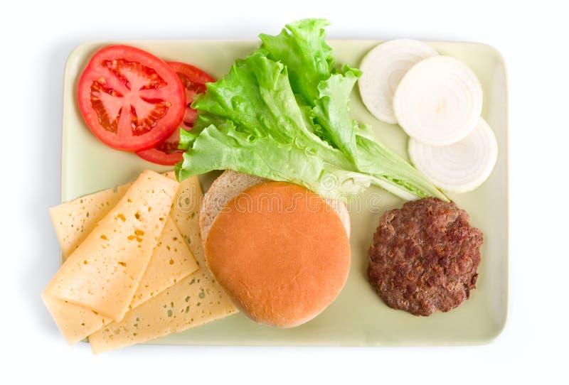 Ingridients del cheeseburger su una zolla fotografia stock libera da diritti