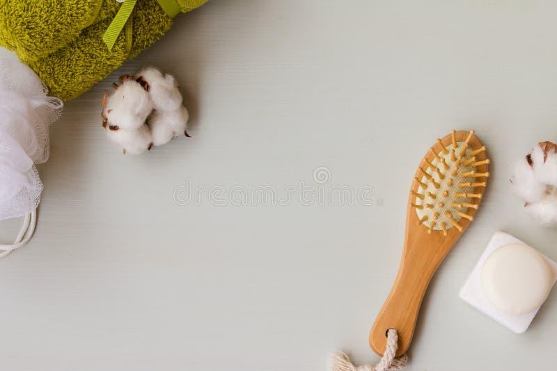 Ingridients della stazione termale su fondo di legno bianco Wisp di rafia, del pettine, del sapone naturale e dell'asciugamano co fotografie stock libere da diritti