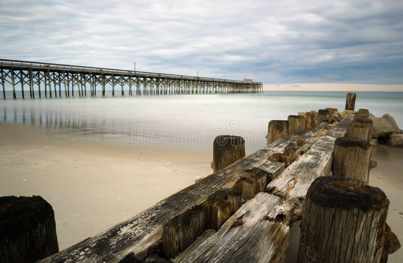 Inguine su una spiaggia in Carolina del Sud con il pilastro nei precedenti immagine stock