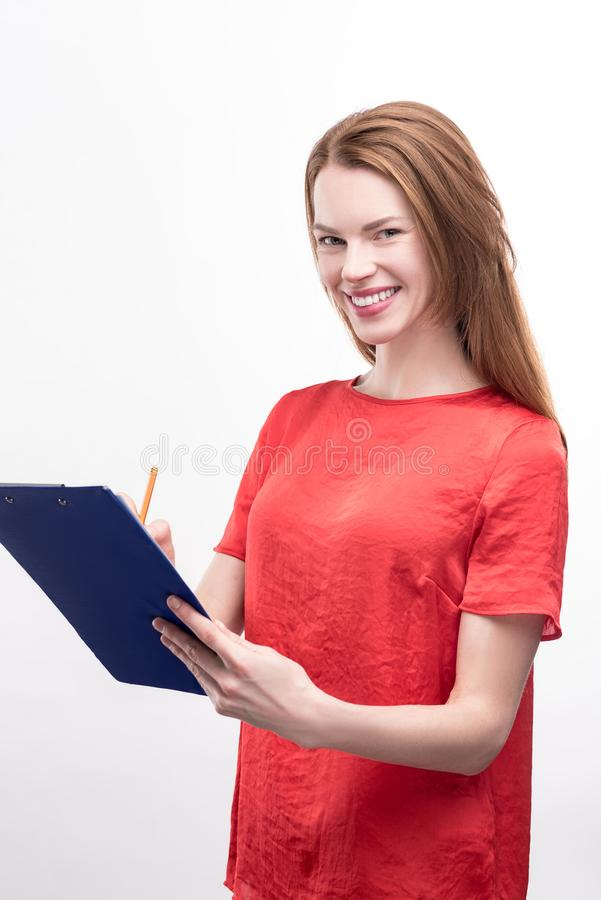 Ingwer-haarige Frau, die Form auf Blatthalter ausfüllt lizenzfreie stockbilder