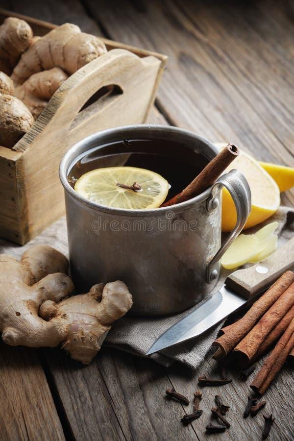 Ingwer Teetasse mit Zitrone und Zimt, Ingwerwurzeln und Zimtstifte auf Küchentisch lizenzfreie stockfotos