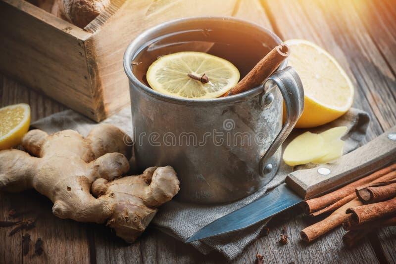 Ingwerentasse mit Zitrone und Zimt, Ingwerwurzeln, Messer- und Zimtstifte auf Küchentisch lizenzfreie stockfotos