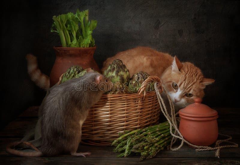 Ingwerkatze macht eine graue Ratte ausfindig, die hinter einem Korb von Artischocken und von Spargel sich versteckt Stilllebenzus stockbild