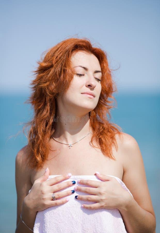 Ingwermädchen mit dem losen Haar und mustert das geschlossene Ein Sonnenbad nehmen am Se lizenzfreie stockfotos