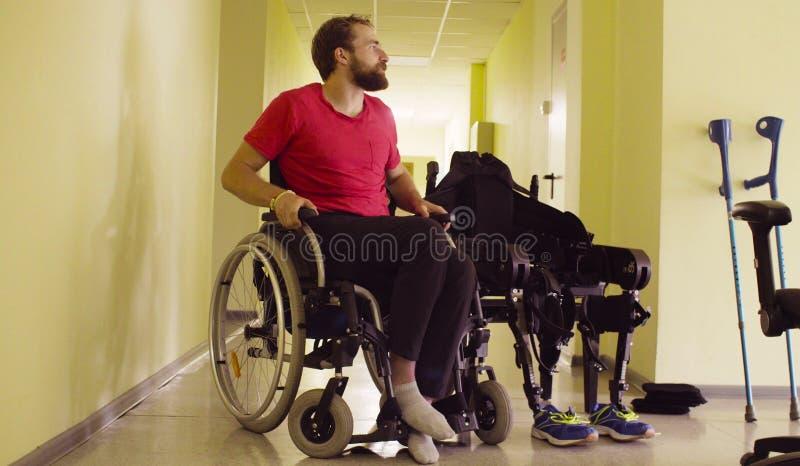 Inhabilite al hombre que se sienta en silla de ruedas en la clínica de la rehabilitación imágenes de archivo libres de regalías