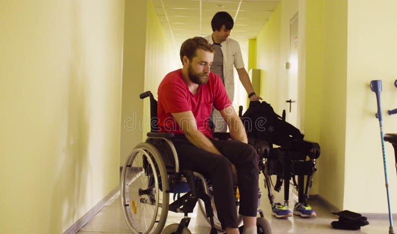 Inhabilite al hombre que se sienta en silla de ruedas en la clínica de la rehabilitación imagen de archivo