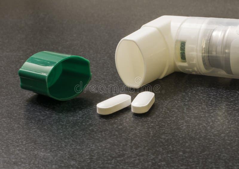 Inhalateur avec deux pilules blanches et chapeau vert sur la surface médicale photographie stock