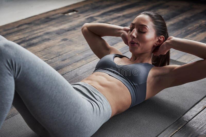 Inhale La vue de la fille avec un corps mince travaille sur les abdos quand elle est allongée sur le sol photographie stock libre de droits