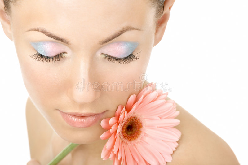 Inhaling flower aroma. Portrait of the beautiful woman blindly and pink gerbera stock image