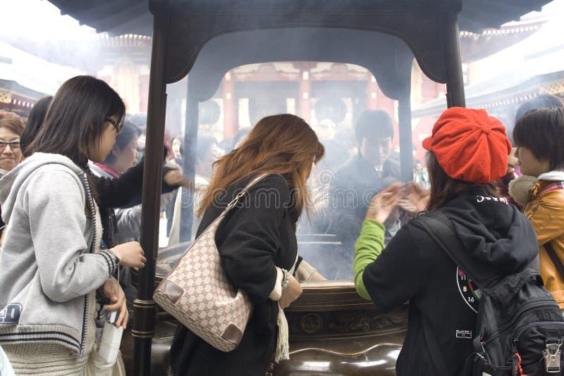 Inhaling incense smoke in Tokyo stock images