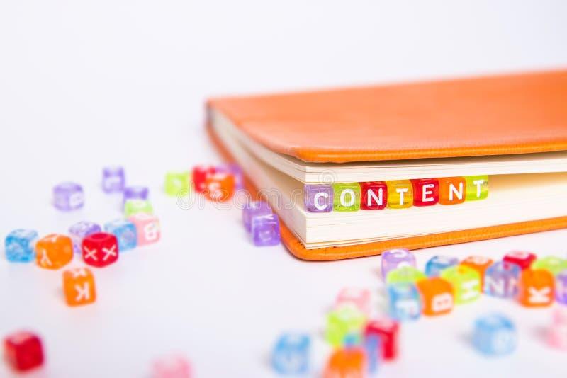 Inhaltswort auf buntem Perlenblock als Bookmark im Buch zufriedenes Marketing-Ideenkonzept lizenzfreie stockfotos