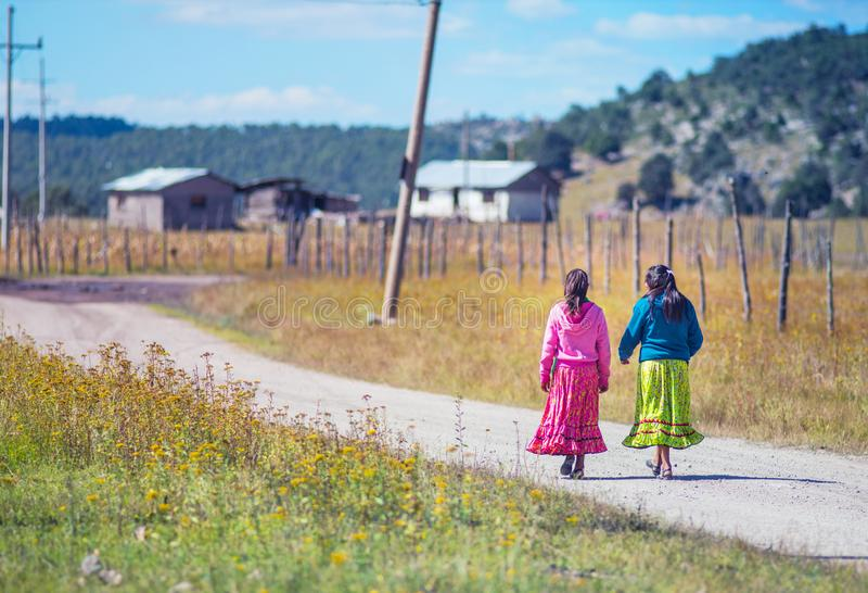 Inheems slecht schoolmeisje in traditionele kleurrijke kledingsgang op de manier aan huis, Mexico, Amerika royalty-vrije stock afbeeldingen