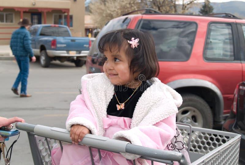 Inheemse Amerikaanse meisjeszitting in een boodschappenwagentje stock afbeeldingen