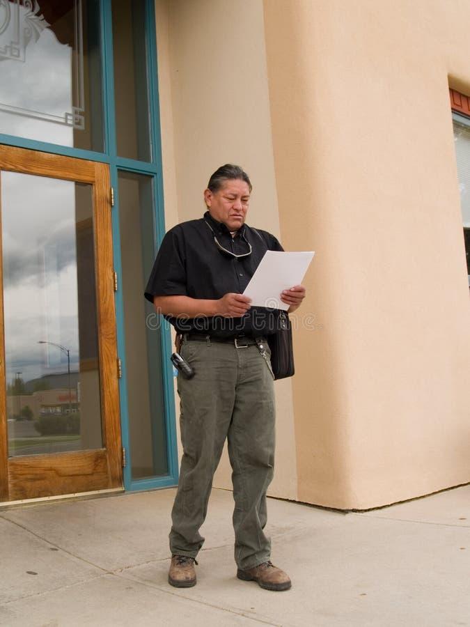 Inheemse Amerikaanse mens die bij documenten kijkt royalty-vrije stock afbeelding