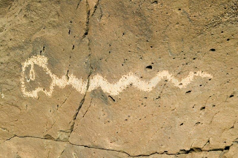 Inheemse Amerikaanse rotstekeningen die een beeld van een slang kenmerken bij Rotstekenings Nationaal Monument, buiten Albuquerqu stock afbeelding