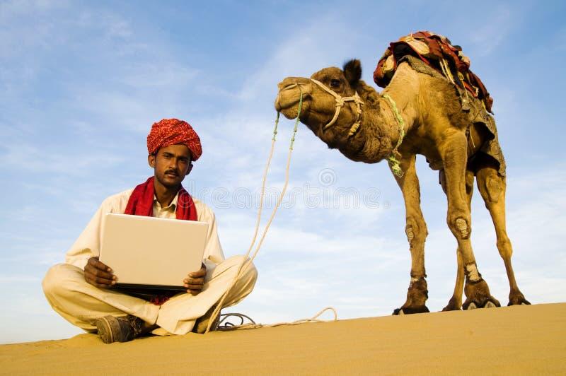 Inheemse Indische Mens met Zijn Laptop uit in een Woestijn stock afbeelding