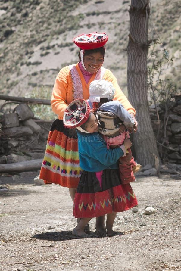 Inheemse Peruviaanse vrouw die en met haar jonge geitjes smilling spelen stock afbeelding