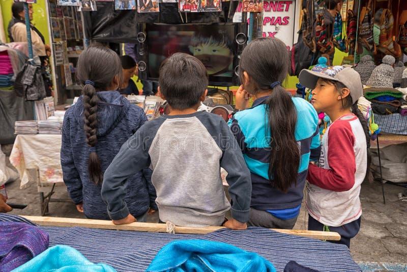 Inheemse quechua kinderen die op televisie letten stock afbeeldingen