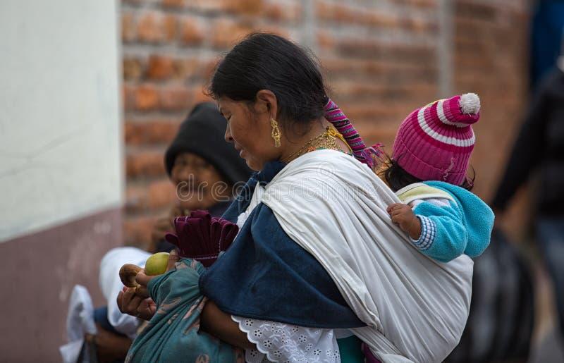 Inheemse quechua vrouwen dragende peuter op haar terug in Ecuador stock afbeelding