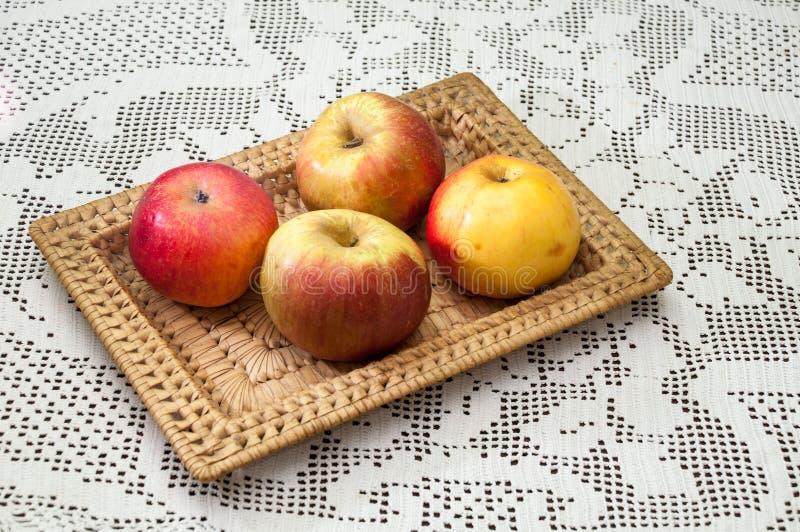 Inhemska äpplen i en vide- korg på broderad bordduk royaltyfri bild