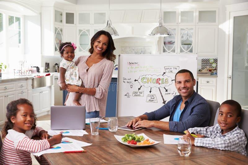 Inhemskt möte i köket, familj som ser till kameran fotografering för bildbyråer