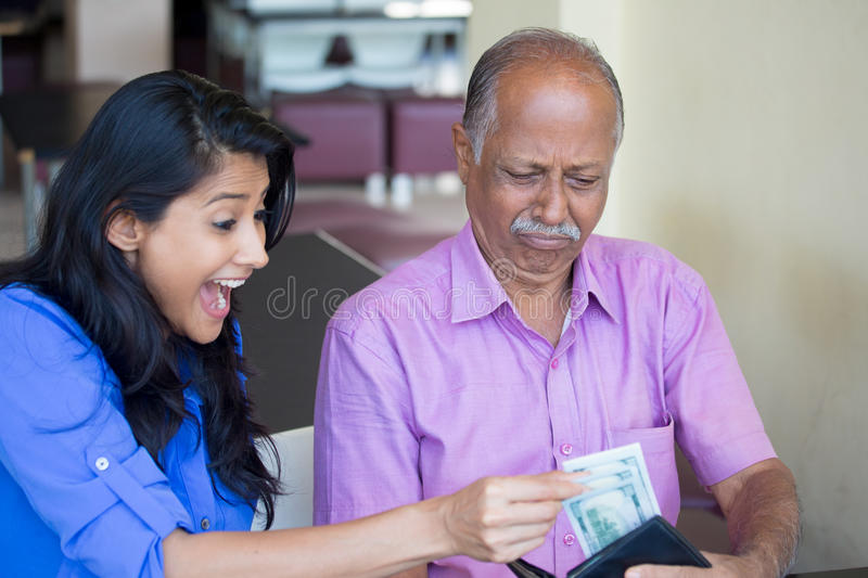 Inherit wealth. Closeup portrait of young pretty women happy to take money from upset man, who is reluctant to give cash dollar bills out, indoors background stock photography